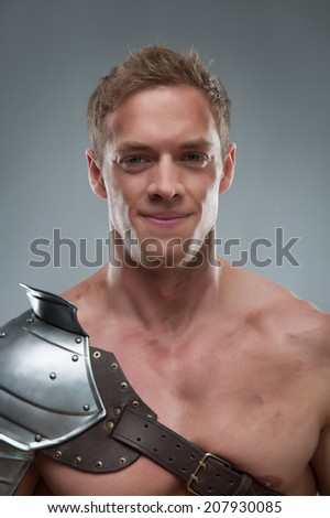 Closeup  portrait of young handsome muscular smiling man gladiator in armour posing  isolated over grey background - stock photo