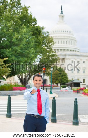 Closeup portrait of young handsome smiling professional, federal employee, politician, businessman, executive, lawyer pointing at you camera gesture, isolated on background Washington DC Capitol usa - stock photo