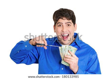Closeup portrait of young happy man, business worker employee, corporate agent representative cutting budget, trimming dollar bills, cash, money with scissors, isolated on white background. Emotions - stock photo
