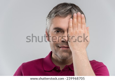 Closeup portrait of young man covering his eye. Portrait of confident adult man covering his eye with hand while isolated on grey - stock photo