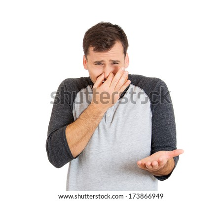 Closeup portrait of young man, disgust on face, pinches his nose, something stinks very bad smell, situation, asking is it you, isolated on white background. Negative emotion facial expression feeling - stock photo