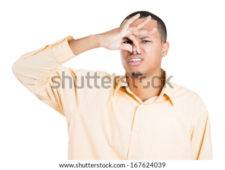Closeup portrait of young man, disgust on his face, pinches his nose looks at you, something stinks, very bad smell, situation, isolated on white background. Negative emotion facial expression feeling