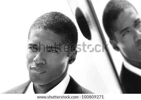 Closeup portrait of young man in black and white against reflective wall - stock photo