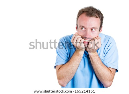 Closeup portrait of young man in blue shirt biting his nails and looking at you with a craving for something or anxious, isolated on white background, space to left. Negative Human facial expressions.