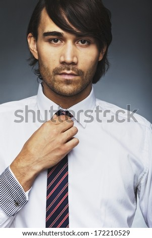 Closeup portrait of young man in formal clothing adjusting his necktie. Handsome business executive wearing tie looking at camera against grey background. - stock photo