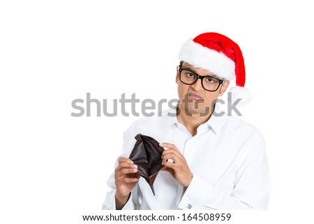 Closeup portrait of young man in red santa claus hat with big black glasses holding up showing empty wallet, isolated on white background with space to left. Negative human emotion facial expression - stock photo