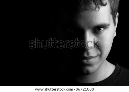 closeup portrait of young man isolated on black background with copyspace - stock photo