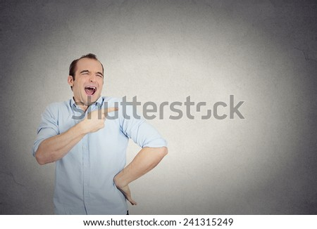 Closeup portrait of young man, laughing, pointing with finger, arms at someone, something, isolated grey wall background. Positive human face expression, emotion, feelings, attitude, approach reaction - stock photo