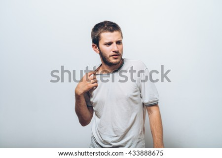 Closeup portrait of young man opening shirt to vent,it's hot. Negative emotion, facial expression, feeling - stock photo