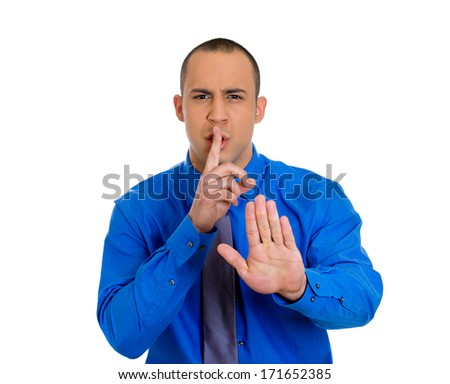 Closeup portrait of young man placing finger on lips to say, shhhhh, be quiet, gesture with hand isolated on white background. Negative facial expression feelings emotions signs symbols, body language - stock photo