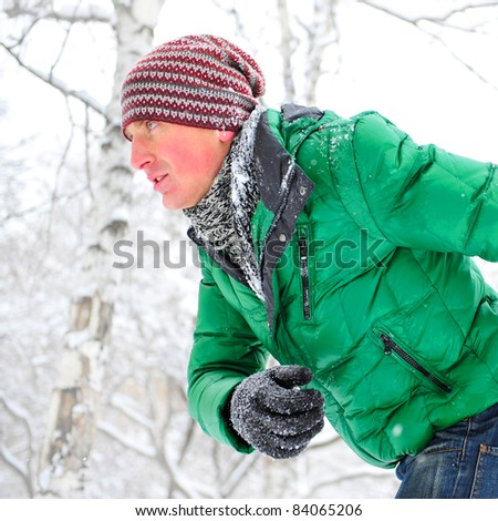 Closeup portrait of young man running in winter park wearing sportswear and looking forward - stock photo