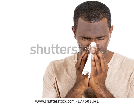 Closeup portrait of young man, sick guy, student, worker patient with allergy, cold blowing his nose, kleenex, looking miserable unwell, isolated on white background. Flu season, vaccination - stock photo