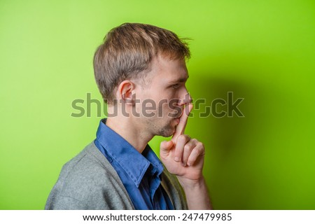 Closeup portrait of young man, student, coach, trainer, worker placing finger on lips shhh, asking to be quiet - stock photo