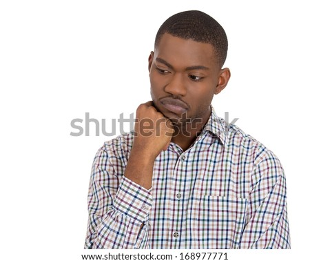 Closeup portrait of young man thinking daydreaming deeply about something chin on hand looking downwards, isolated on white background. Negative emotion facial expression feeling