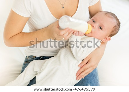 Closeup portrait of young mother holding her baby and feeding with milk from bottle