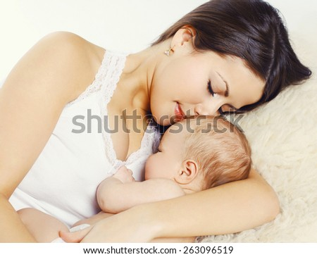 Closeup portrait of young mother sleeping with baby at home