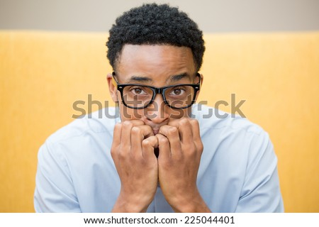 Closeup portrait of young nerdy unhappy guy with big black glasses and blue shirt, wide open eyes, biting his nails and looking to camera with a craving for something or anxious, worried. - stock photo