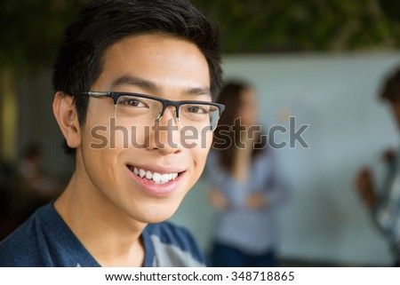 Closeup portrait of young positive asian man in glasses lookng camera - stock photo