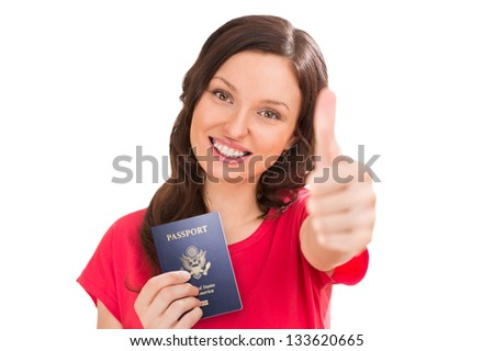 Closeup portrait of young positive woman holding passport and thumbs up - stock photo