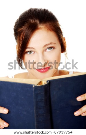 Closeup portrait of young pretty caucasian girl  holding open book over white background.
