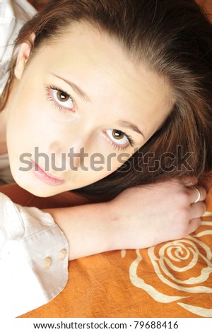 Closeup portrait of young pretty girl laying on her bed at her modern stylish apartment - stock photo