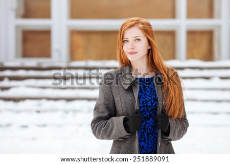 Closeup portrait of young pretty redhead lady in blue dress and grey coat at winter outdoors - stock photo