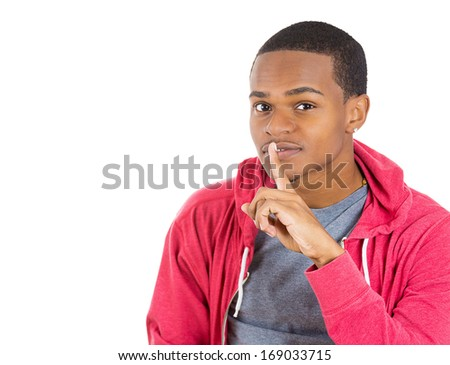 Closeup portrait of young serious man placing finger on lips as if to say, shhhhh, be quiet, silence , isolated on white background with. Negative facial expression, human emotions signs and symbols - stock photo