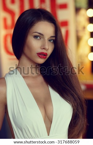 Closeup portrait of young sexy stunning woman posing in white evening dress with beautiful decollete, dark long hair, and red lips posing in dressing room. Fashion vogue style photo - stock photo