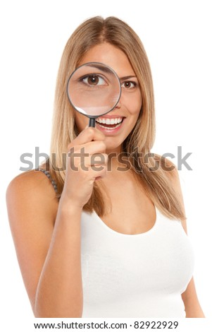 Closeup portrait of young smiling female looking through the loupe at you, isolated on white background - stock photo