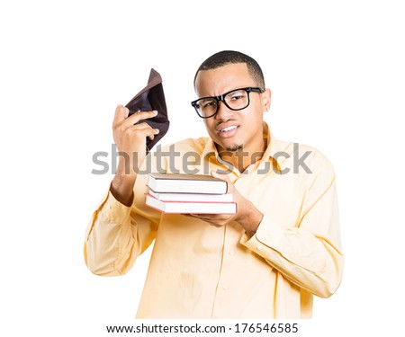Closeup portrait of young student man holding books in one hand and empty wallet in the other, looking distressed that he has no more money is broke, isolated on white background. Education value - stock photo