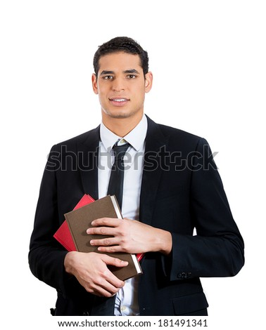Closeup portrait of young successful, confident, corporate employee, business worker in black suit and tie, holding stack of books, isolated on white background. Power of education and higher learning