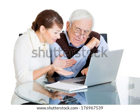 Closeup portrait of young technology savvy, frustrated woman showing confused senior older elderly man with eyeglasses how use laptop isolated on white background. Generation gap difference concept