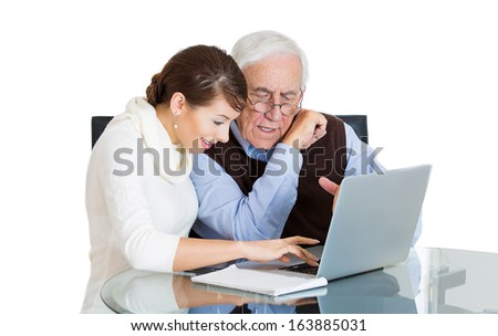 Closeup portrait of young technology savvy woman helping showing confused senior older mature elderly man with eyeglasses how use laptop on table isolated on white background. Generation gap concept - stock photo