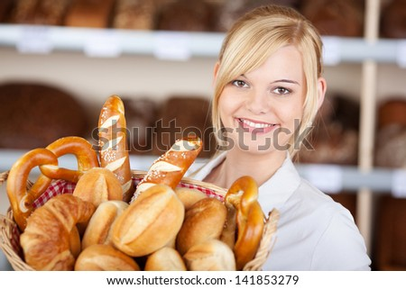 Closeup portrait of young waitress with bread basket in cafe - stock photo