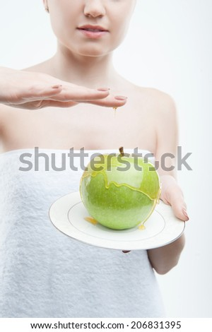 Closeup portrait of young woman in towel holding a plate with green apple covered with honey, isolated on white. Concept of healthy nutrition, beauty and diet - stock photo