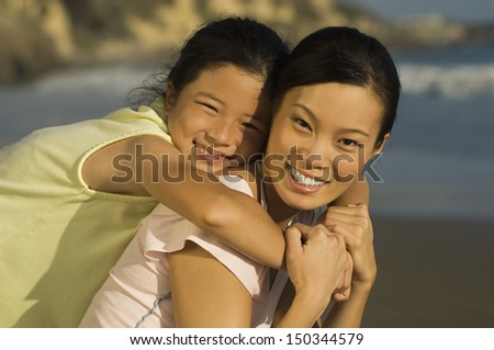 Closeup portrait of young woman piggybacking daughter on beach
