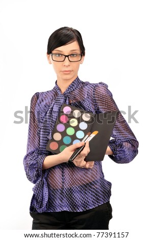 Closeup portrait of young woman professional visagiste holding brushes and eyeshadows in her arms wearing glasses and thinking about she`s new idea. Isolated on white background - stock photo