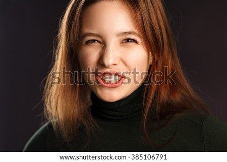 Closeup portrait of young woman showing her teeth and hissing - stock photo