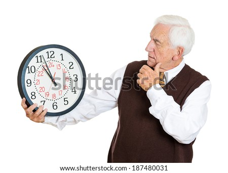 Closeup portrait old business man, funny looking elderly guy, holding clock, stressed, running out, pressured by lack time, aging, late meeting isolated white background. Negative emotion expression - stock photo