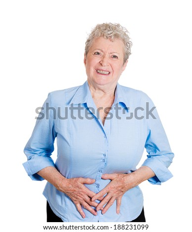 Closeup portrait old business woman, elderly boss, corporate worker, unhealthy grandmother doubling over in stomach pain, isolated white background. Human emotions, facial expressions. Acute abdomen - stock photo