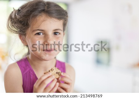 closeup portrait on a little girl eating a cookie - stock photo