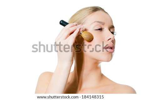 closeup portrait on young beautiful sexy woman applying blush powder or rouge on white background