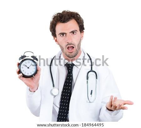Closeup portrait, overwhelmed with busy schedule, unhappy male health care professional doctor, nurse, dentist with stethoscope holding alarm clock running out of time, isolated white background - stock photo