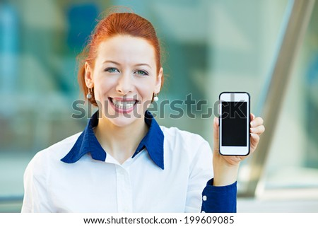 Closeup portrait, photo attractive, happy, smiling young business woman presenting, holding smartphone, screen, isolated background corporate office windows. Positive human face expression, emotions - stock photo