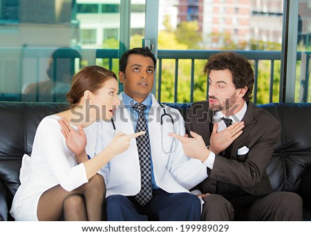Closeup portrait psychiatrist sitting on black couch caught in between angry couple man, woman trying to push them back in doctor's office isolated city urban background. Negative emotion. Healthcare  - stock photo