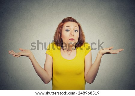 Closeup portrait puzzled clueless young woman with arms out asking what is problem who cares so what I don't know isolated grey background. Negative human emotion face expression reaction perception - stock photo