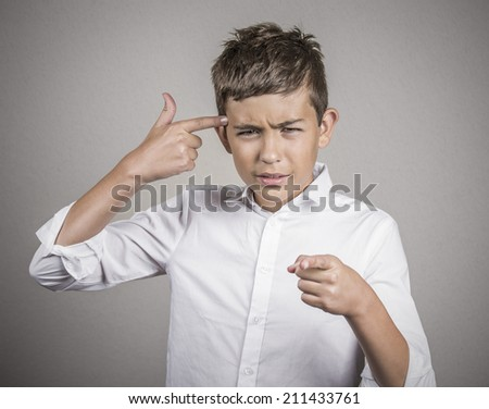 Closeup portrait rude difficult angry young man gesturing with finger against his temple, are you crazy? Isolated grey wall background. Negative human emotion, facial expression, feeling body language - stock photo