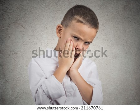 Closeup portrait sad, depressed, alone, unhappy, gloomy child boy resting his face on hands, isolated grey wall background. Negative human emotion face expression feeling life perception body language - stock photo