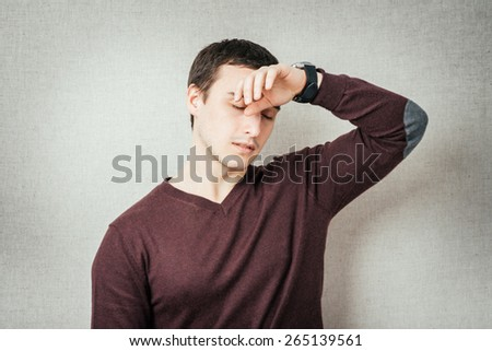 Closeup portrait sad depressed stressed, alone disappointed gloomy young man having headache, regrets, many thoughts isolated orange background. Human emotion facial expression feeling body language - stock photo