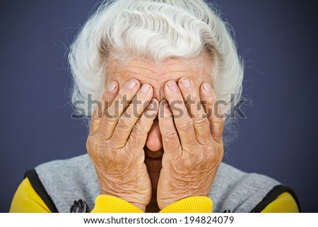 Closeup portrait sad depressed, stressed, thoughtful, senior, old woman, gloomy, worried,  covering her face, isolated blue background. Human face expressions, emotion, feelings, reaction, attitude - stock photo